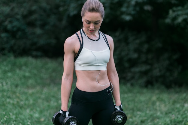 Attractive strong woman in sportswear holds dumbbells in her arms standing outside