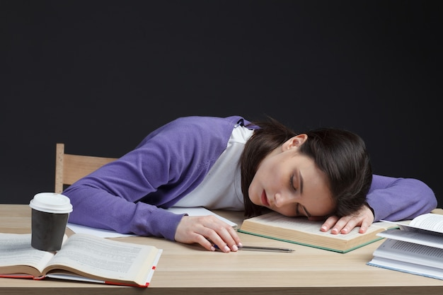 Attractive student adult woman slipping on class desk on education books isolated