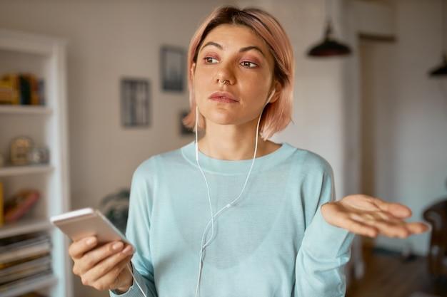 Attraente studentessa che utilizza auricolari e set di microfono mentre comunica online con un amico tramite chat video su smart phone, discutendo di piani, gesticolando.