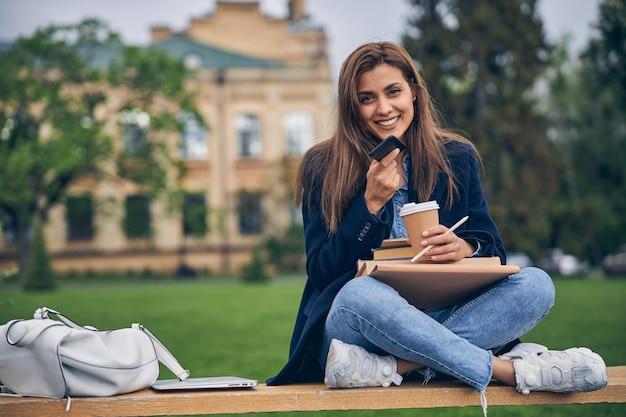 책과 커피와 함께 벤치에 앉아있는 동안 전화로 얘기하는 캐주얼 옷에 매력적인 학생