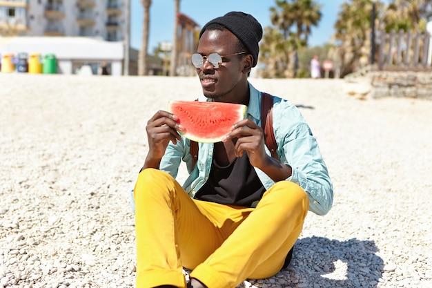 魅力的な学生が大学の後に都会のビーチでリラックス