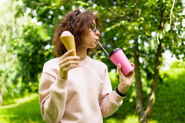 Привлекательная студентка с чашкой кофе и мороженым гуляет в весеннем парке во время обеденного перерыва