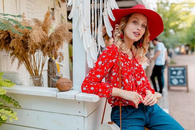 Привлекательная стильная блондинка улыбается женщина в соломенной красной шляпе и блузке летняя мода наряд кафе