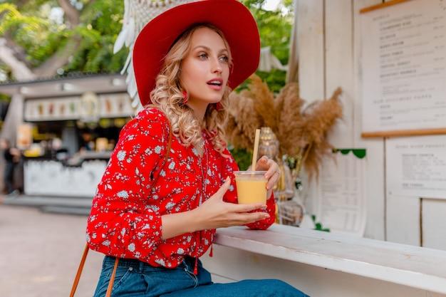 밀짚 빨간 모자와 블라우스 여름 패션 복장 천연 과일 칵테일 스무디를 마시는 매력적인 세련된 금발 웃는 여자