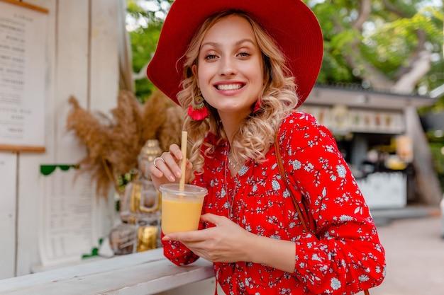 わらの赤い帽子とブラウスの夏のファッション衣装でナチュラルフルーツカクテルスムージーを飲む魅力的なスタイリッシュな金髪の笑顔の女性