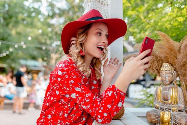 밀짚 빨간 모자와 블라우스 여름 패션 복장 스마트 폰 카페를 사용하여 들고 매력적인 세련된 금발 웃는 여자