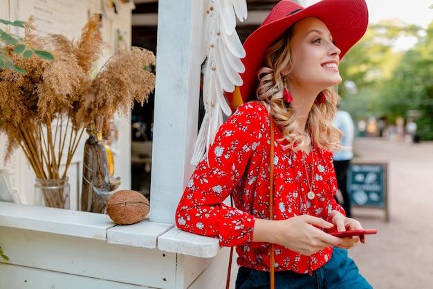 魅力的なスタイリッシュな金髪の笑顔の女性は、スマートフォンのカフェを使用して保持しているわらの赤い帽子とブラウスの夏のファッション衣装で