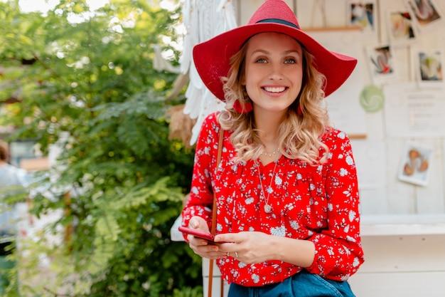 Привлекательная стильная блондинка улыбается женщина в соломенной красной шляпе и блузке летней моды наряд, держащийся с помощью смарт-телефонного кафе