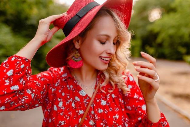 わらの赤い帽子とブラウスの夏のファッションの衣装で魅力的なスタイリッシュな金髪の笑顔の女性
