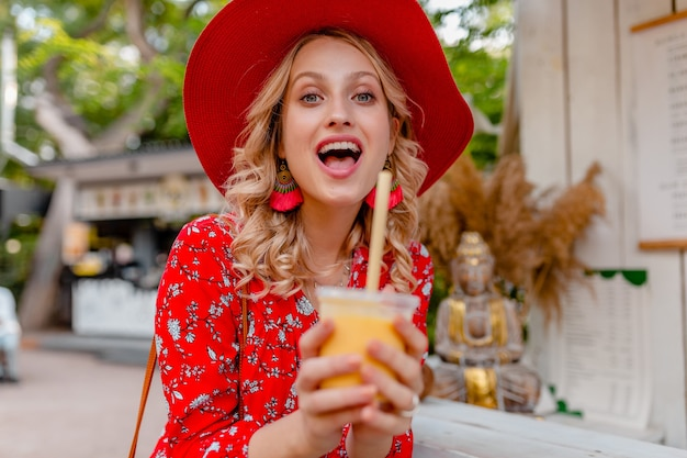 Attractive stylish blond smiling woman in straw red hat and blouse summer fashion outfit drinking natural fruit cocktail smoothie