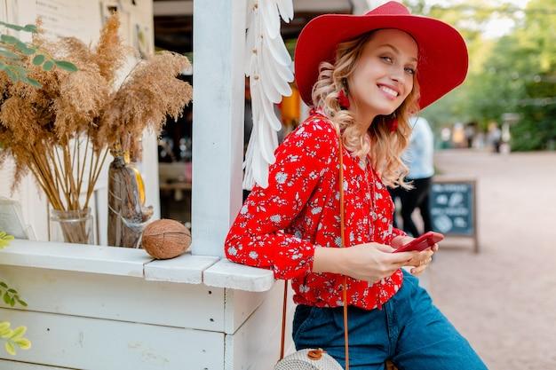 Attraente donna sorridente bionda elegante in cappello rosso di paglia e camicetta vestito di moda estiva che tiene utilizzando smart phone cafe
