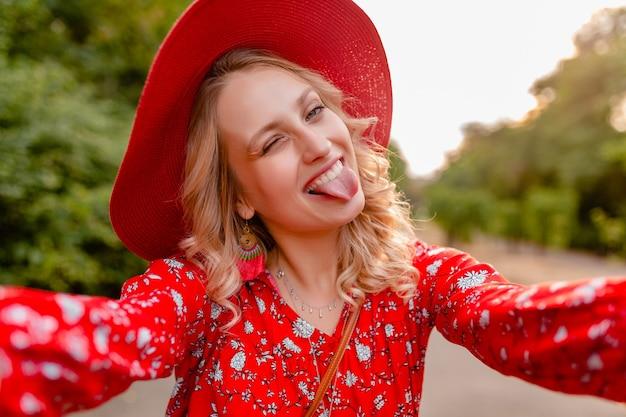 Attraente donna bionda alla moda sorridente in cappello rosso di paglia e camicetta vestito di moda estiva prendendo selfie foto