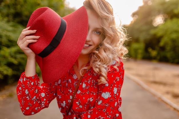 Donna sorridente bionda elegante attraente in cappello rosso di paglia e vestito di moda estiva camicetta