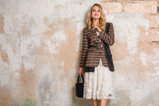 Attractive stylish blonde smiling woman in checkered jacket against wall in street