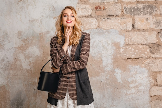 Attractive stylish blonde smiling woman in checkered jacket walking against wall in street