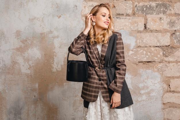 Привлекательная стильная блондинка улыбается женщина в клетчатой куртке, идя против стены на улице
