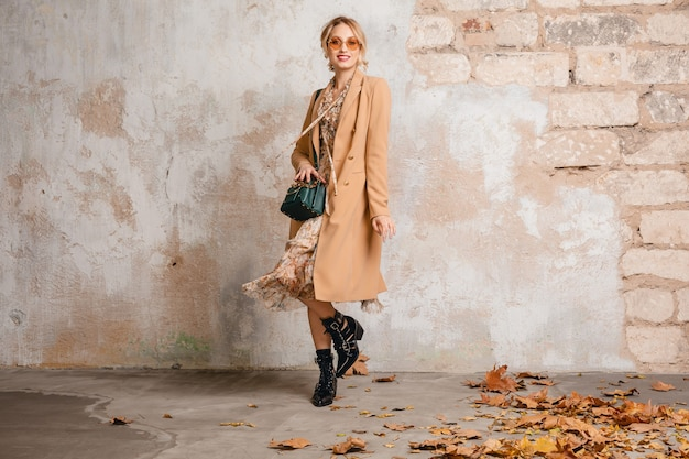 Attractive stylish blonde woman in beige coat walking in street against vintage wall