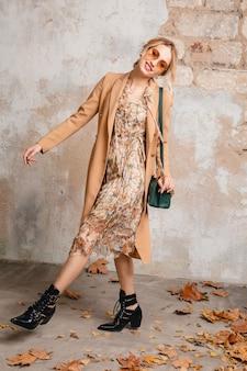 Attractive stylish blonde woman in beige coat walking in street against vintage wall