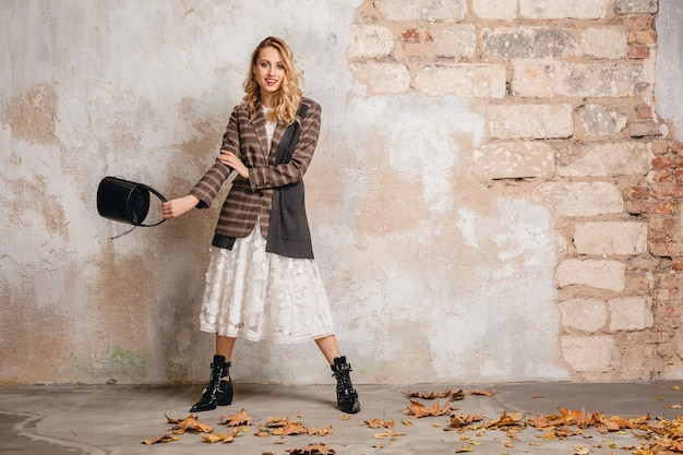 Attractive stylish blonde woman in checkered jacket walking against wall in street