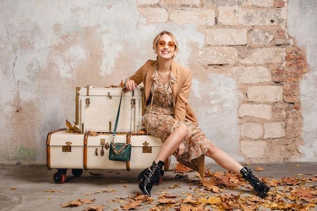 거리에서 벽에 가방에 앉아 베이지 색 코트에 매력적인 세련된 금발의 여자