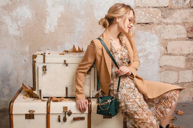 通りの壁にスーツケースの上に座っているベージュのコートで魅力的なスタイリッシュなブロンドの女性
