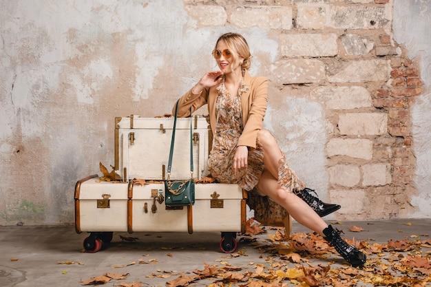 Привлекательная стильная блондинка в бежевом пальто гуляет по улице против старинной стены