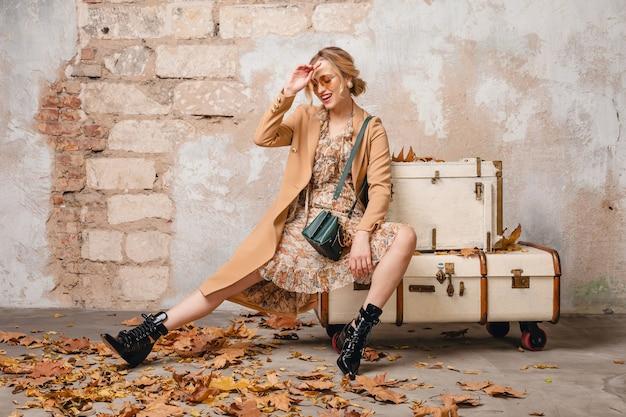ヴィンテージの壁に対して通りを歩くベージュのコートで魅力的なスタイリッシュなブロンドの女性