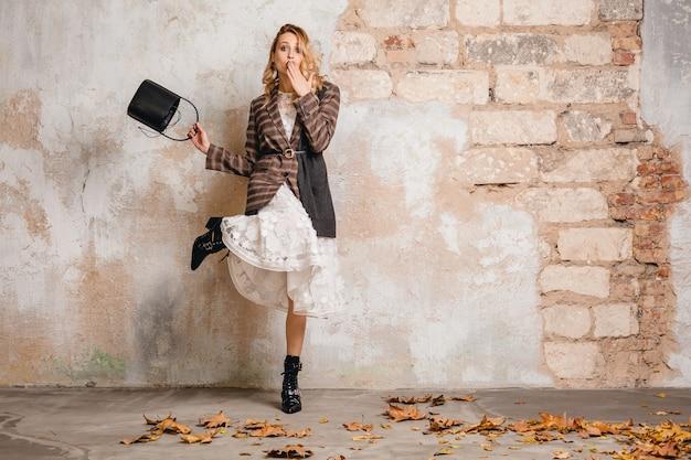 거리에서 벽에 걸어 체크 무늬 재킷에 매력적인 세련된 금발의 여자
