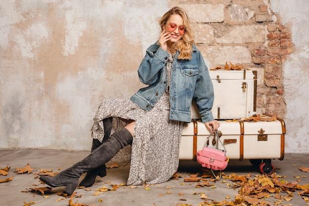通りの壁に向かって歩くジーンズと特大のジャケットの魅力的なスタイリッシュなブロンドの女性