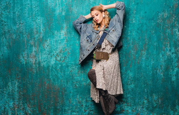 Attractive stylish blonde woman in jeans and oversize jacket walking against vintage green wall in street