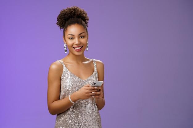 Привлекательная стильная уверенно афро-американская женщина в серебряном блестящем платье, держащая смартфон, обменивающийся сообщениями, прокручивая интернет-гаджет, глядя на счастливую счастливую камеру, стоящую на синем фоне, радуясь.