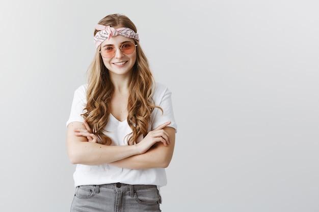 Привлекательная, стильная уверенная блондинка улыбается со скрещенными руками в солнцезащитных очках