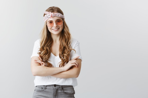 Attractive, stylish confident blond girl smiling with arms crossed in sunglasses
