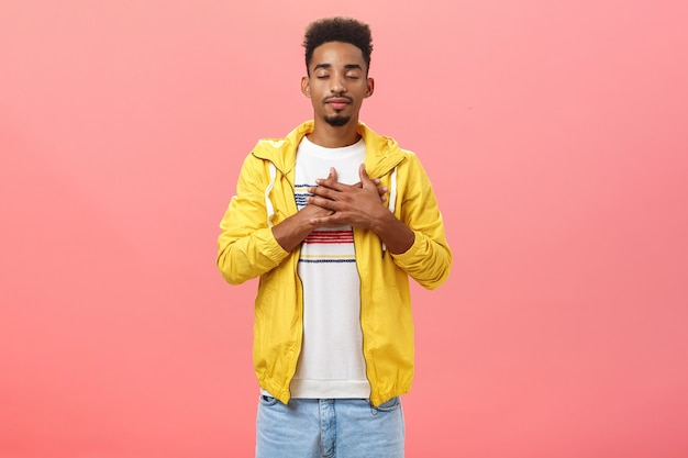 Attractive and stylish dark-skinned guy feeling warm and calm feelings inside holding hands on heart closing eyes and smiling with relieved comfort expression standing over pink wall in trendy outfit