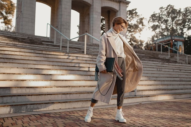 メガネ、バッグ、白いブーツを身に着けているエレガントなスタイルのコートで通りを歩く魅力的なスタイリッシュなファッショナブルな女性