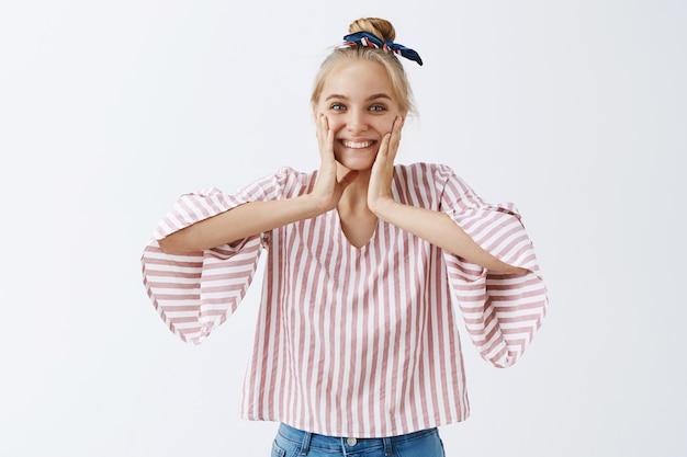 Attraente ragazza alla moda in posa contro il muro bianco