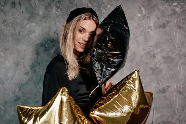 Attraente ragazza alla moda con capelli biondi vestiti di neri vestiti preparando per la festa di natale