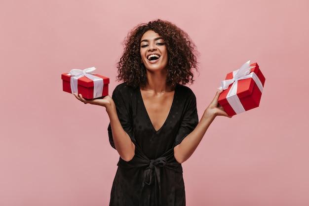 Привлекательная стильная девушка с крутой вьющейся прической в темной одежде в горошек смеется, смотрит в камеру и держит подарочные коробки