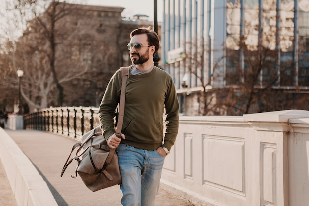 Attractive stylish hipster man walking in city street with leather bag wearing sweatshot and sunglasses, urban style trend, sunny day