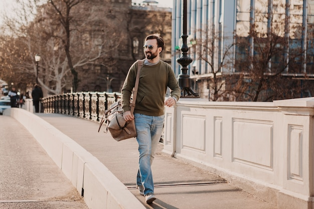 Uomo attraente alla moda hipster che cammina nella strada della città con borsa in pelle che indossa tuta e occhiali da sole, tendenza di stile urbano, giornata di sole