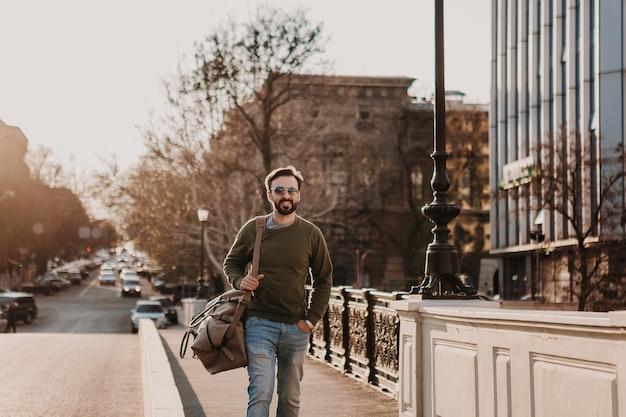 Привлекательный стильный хипстерский мужчина, идущий по городской улице с кожаной сумкой в поте и солнцезащитных очках, тенденция городского стиля, солнечный день