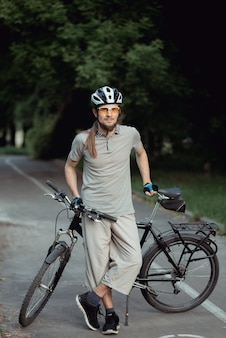 Attractive stylish man posing next to his bicycle on the park. he is holding his bicycle.