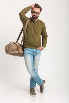 Привлекательный стильный мужчина-путешественник изолирован, стоя с сумкой, красавец, одетый в джинсы и потеет