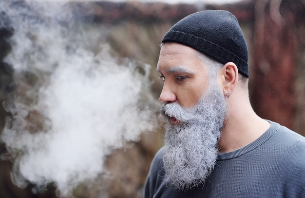 Attractive stylish man with grey beard and mustache releases