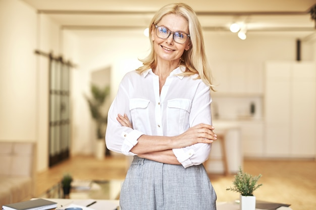Attractive stylish mature blonde businesswoman looking at camera with a friendly smile while