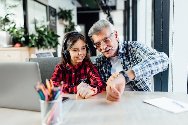 Привлекательный стильный дедушка с короткой бородой с помощью смартфона с внучкой
