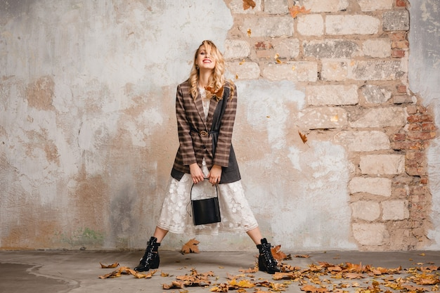 Attractive stylish smiling blonde woman in checkered jacket walking against wall in street