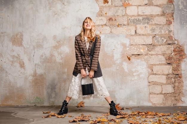 거리에서 벽에 걸어 체크 무늬 재킷에 매력적인 세련된 웃는 금발의 여자