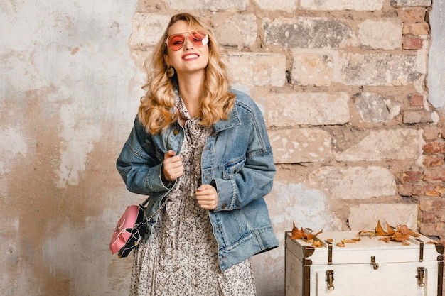 Attractive stylish smiling blonde woman in jeans and oversize jacket walking against wall in street