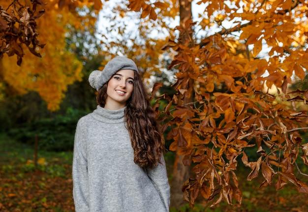 Привлекательная стильная улыбающаяся девушка с вьющимися волосами, гуляющая в парке, одетая в теплые серые осенние модные моды, в шляпе берет.